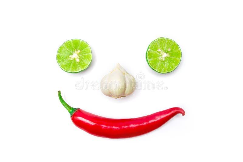 从红辣椒、大蒜和石灰的菜微笑的面孔在白色背景 免版税库存照片