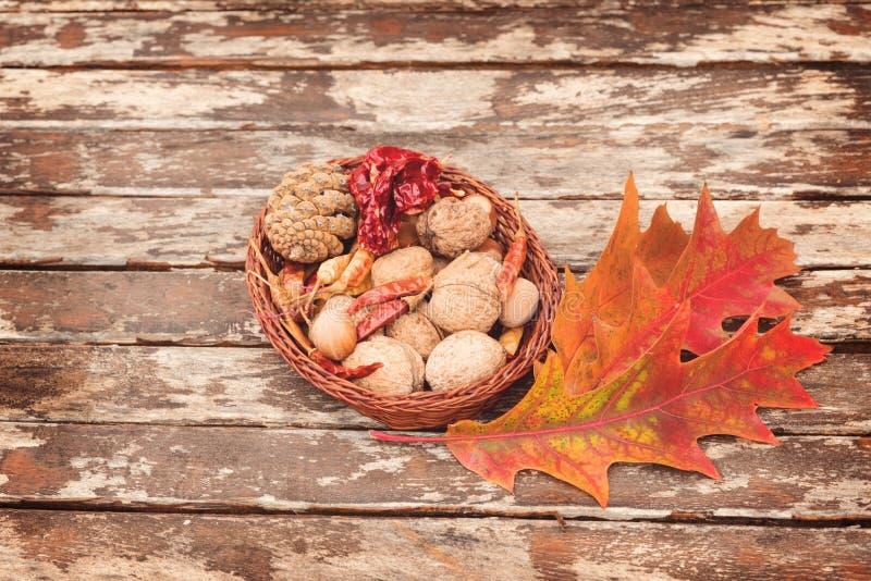 红辣椒、核桃、栗子和巧克力精炼机在一个木碗在老土气木桌上与秋叶 免版税库存照片