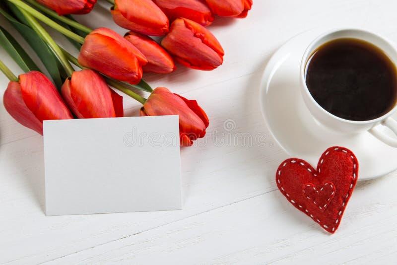 红郁金香,心脏,白桌上的咖啡 母亲节春假早礼 复制空间 库存照片
