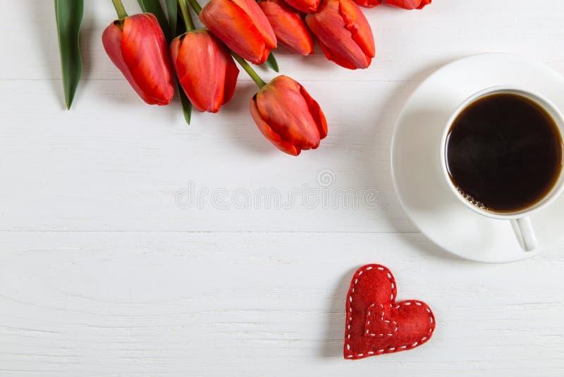 红郁金香,心脏,白桌上的咖啡 母亲节春假早礼 复制空间 免版税库存图片
