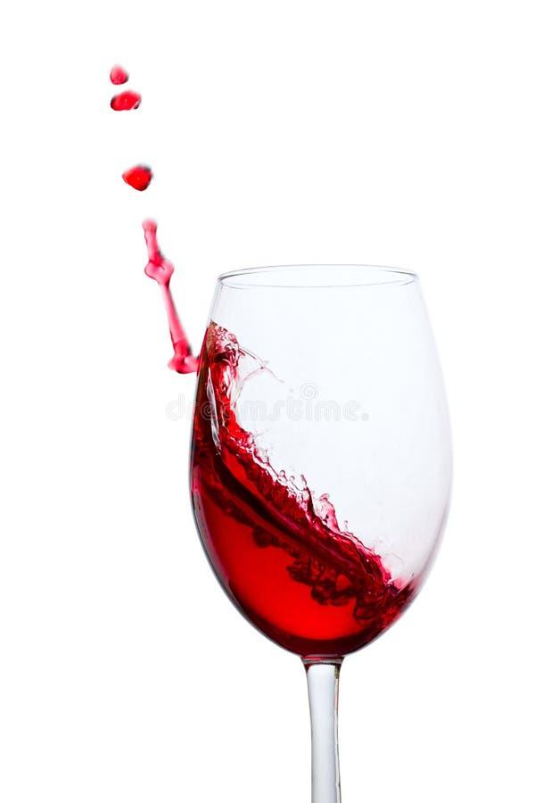 红酒令人激动的波浪被触击反对玻璃的边缘 免版税库存图片