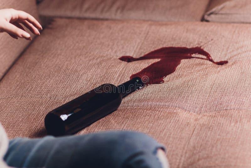 红酒在一个棕色长沙发沙发溢出了 黑暗的瓶红酒落下了 免版税库存照片