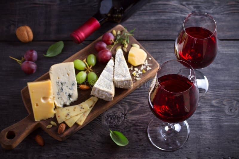 红酒用在砧板的乳酪 酒和食物概念 库存照片