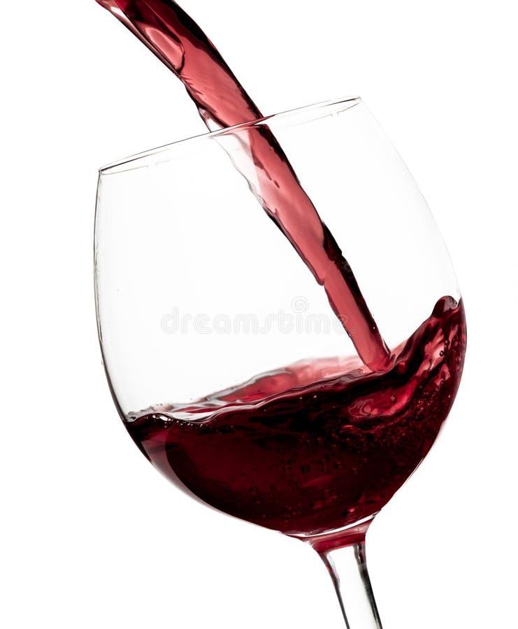 红酒美丽的飞溅在一块玻璃的在白色背景 免版税图库摄影