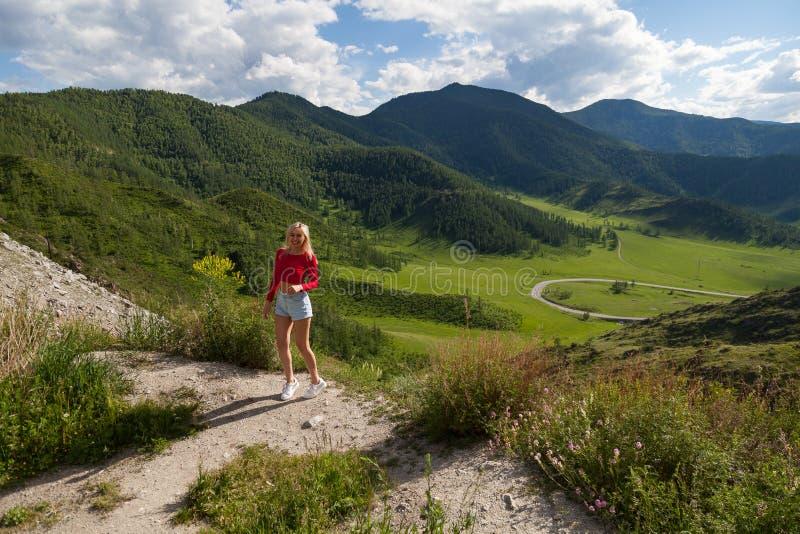 红顶和蓝色短裤的一个女孩在阿尔泰山的峭壁边缘,下面是与树和草的绿色领域 免版税库存图片