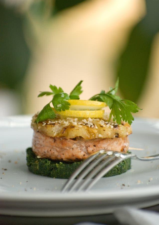 红鲑鱼鱼或鳟鱼牛排内圆角在菠菜坐垫 免版税库存照片