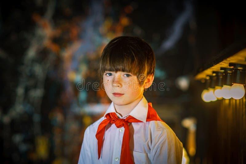 红头发人可爱的男孩穿戴了象与红色领带的苏联先驱 免版税库存照片