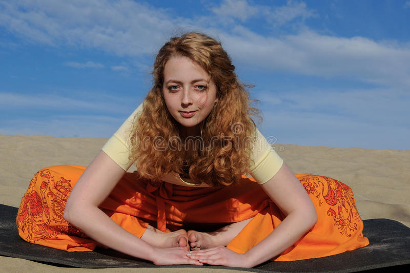 年轻红头发人妇女在purna titli瑜伽姿势坐beac 库存照片