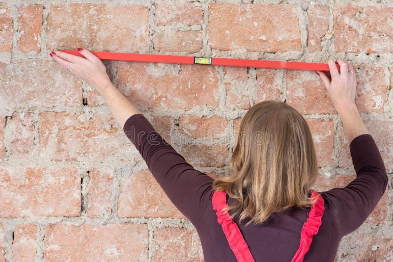 红头发人少妇使用一个水平仪 免版税图库摄影