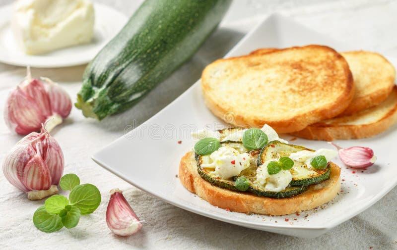 纤巧bruschetta用油煎的或被烘烤的夏南瓜、无盐干酪乳酪、大蒜、薄菏和香料 免版税库存照片