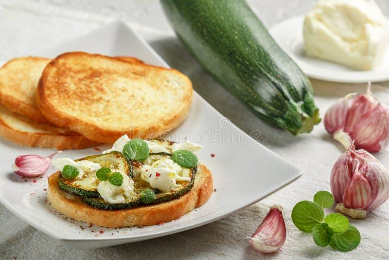 纤巧bruschetta用油煎的或被烘烤的夏南瓜、无盐干酪乳酪、大蒜、薄菏和香料 库存照片