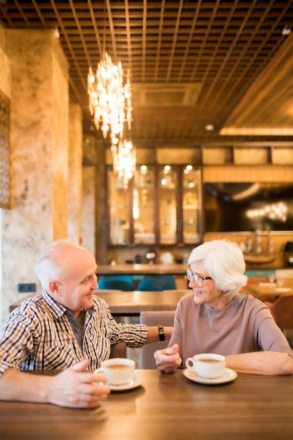 约会在咖啡馆的快乐的资深夫妇 免版税库存图片