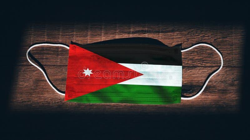 约旦国旗,医疗,手术,黑木背景防护面具 冠状病毒Covid-19,预防感染, 库存图片