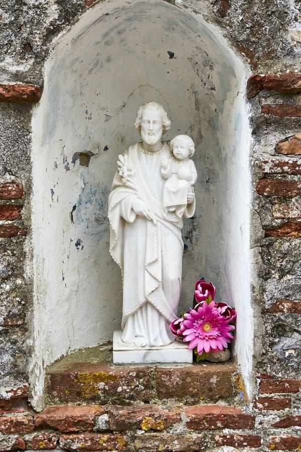 约瑟夫宗教雕象有崇拜者奉献物的以形式 免版税图库摄影