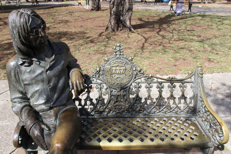 约翰・列侬Bronse雕象一条长凳的在哈瓦那,古巴城市公园  免版税图库摄影
