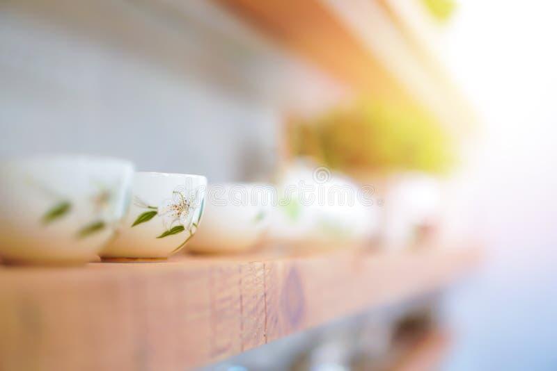 约翰・利利在豪华茶的花纹花样在线的木架子被安排与生动的阳光作用 图库摄影