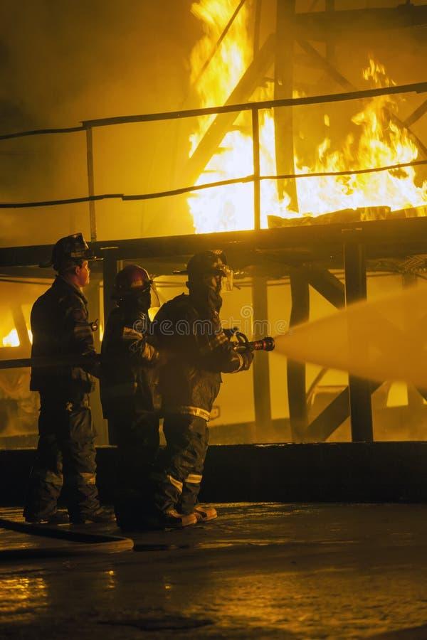 约翰内斯堡,南非- 5月,喷洒水的2018名消防队员在灼烧的结构在一消防训练锻炼期间 库存图片