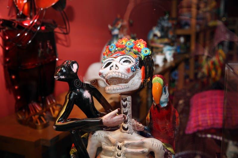 纪念品店窗口,墨西哥雕塑滑稽的女性头骨特写镜头 免版税图库摄影