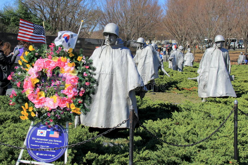 纪念品花圈和旗子临近站立在粗糙的地面,韩战退伍军人的纪念品,华盛顿特区的战士雕象, 2015年 免版税库存照片