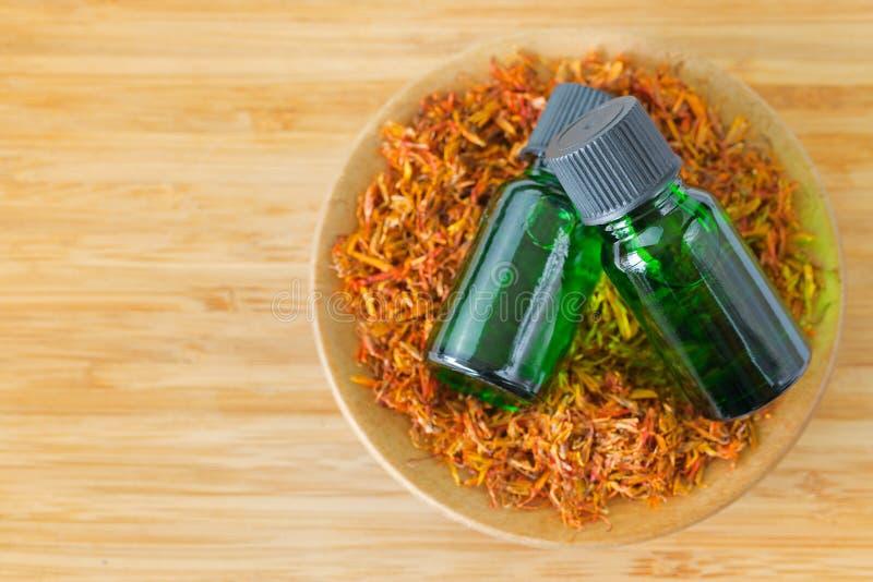 纯净的在绿色瓶的红花根本集中油萃取物 图库摄影