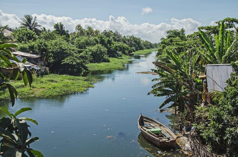 纯净的孩子在肮脏的河,马达加斯加设法抓有些鱼 库存照片