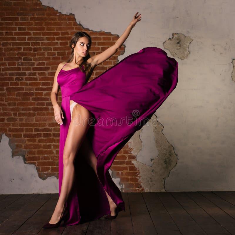 纯净的干净的摆在与pinl柔滑的挥动的礼服的秀丽俏丽的妇女 免版税库存图片