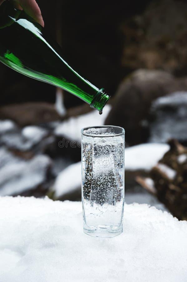 纯净的矿泉水从一个玻璃绿色瓶倾吐入直到最后下落的一个清楚的玻璃烧杯 图库摄影