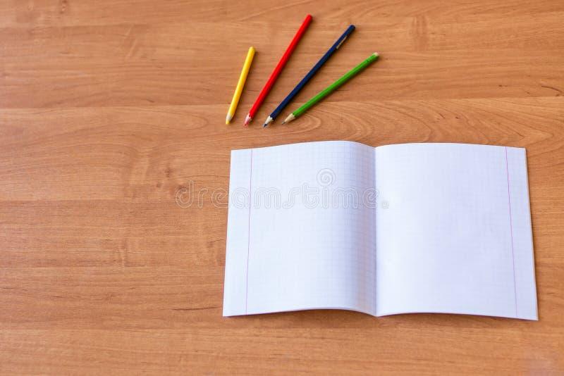 纯净的noteboks和五颜六色的铅笔在木书桌上 学校教育的概念 免版税库存照片