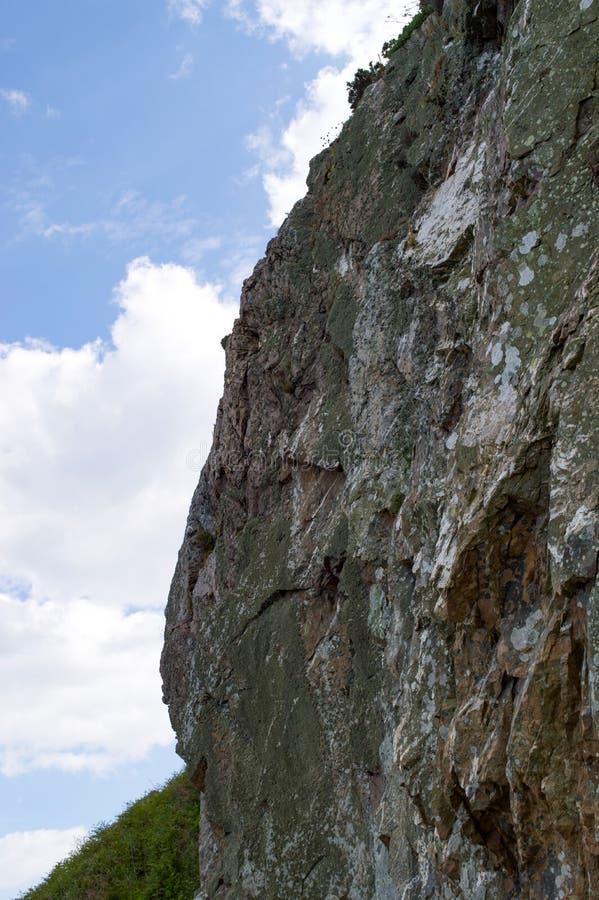 纯粹陡峭的岩石峭壁面孔在威克洛,有天空蔚蓝和白色云彩的爱尔兰 库存照片
