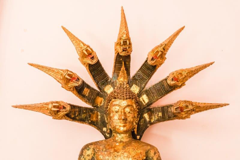 纳卡语美丽的金黄被加冠的菩萨雕象有在他的头的七纳卡人 在寺庙 免版税库存照片