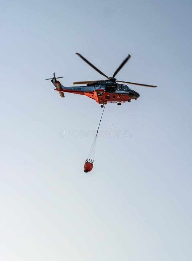纳尔瓦,爱沙尼亚- 2018年7月27日:消防部门的直升机有消防桶的在投入参与 免版税库存图片
