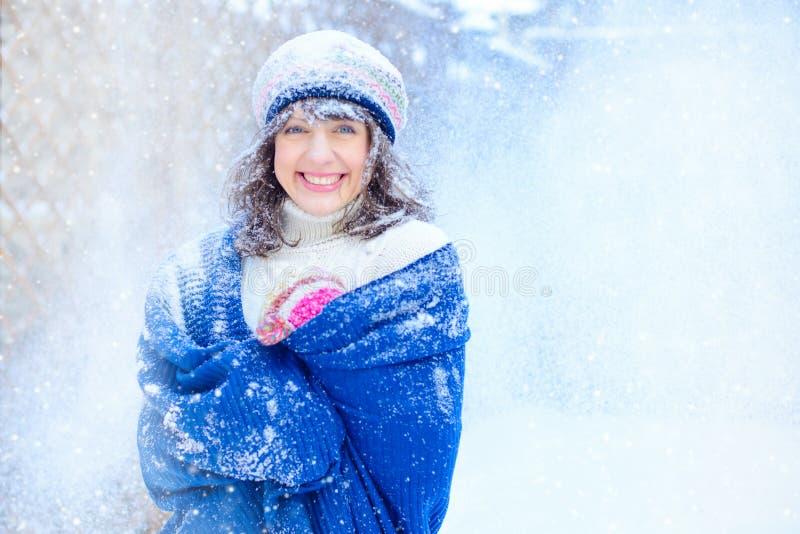 纵向冬天妇女年轻人 笑秀丽欢悦式样的女孩接触她的面孔皮肤和,获得乐趣在冬天公园 义卖市场 免版税库存照片