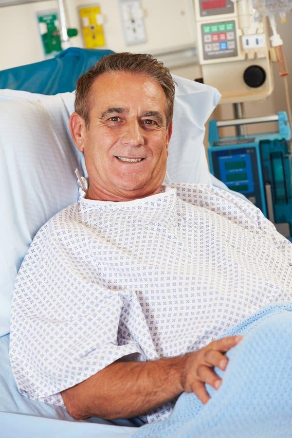 纵向男性耐心放松在医院病床上 库存图片