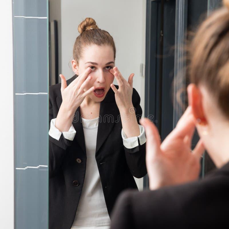纵容检查她的在镜子的美丽的年轻女商人染睫毛油 免版税库存图片