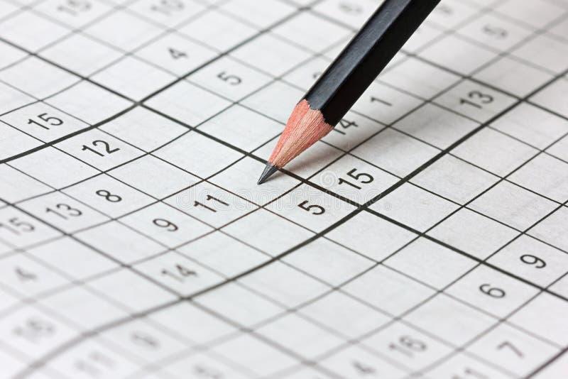 纵横填字谜sudoku和铅笔 免版税库存图片