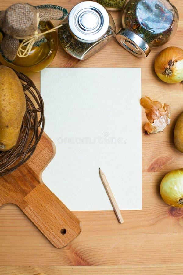 纸、铅笔、水罐橄榄油,土豆、葱、切板和香料 图库摄影