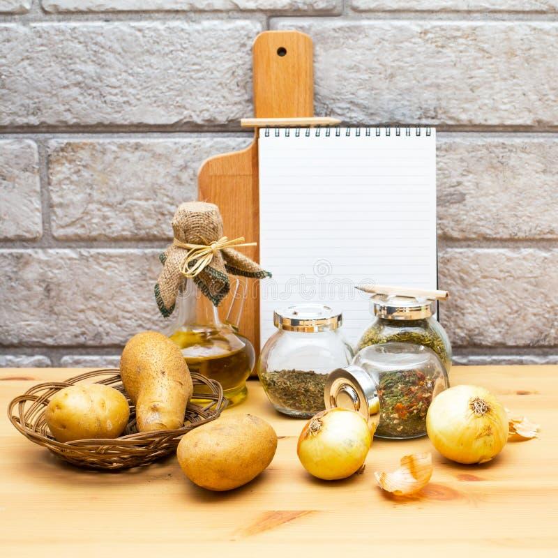 纸、铅笔、水罐橄榄油,土豆、葱、切板和香料 库存照片
