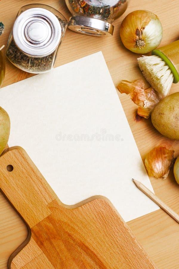 纸、铅笔、水罐橄榄油,土豆、葱、切板和香料 库存图片