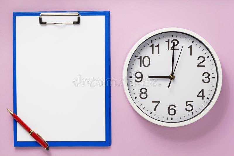 纸剪贴板和壁钟在抽象背景 库存照片