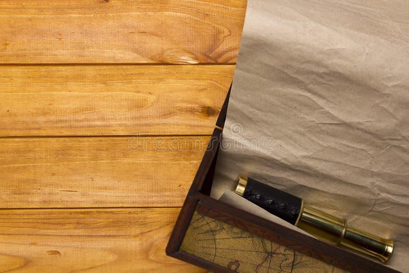 纸卷和望远镜在老箱子 图库摄影