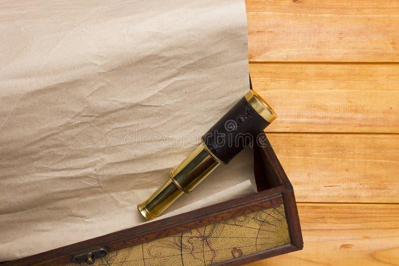 纸卷和望远镜在老箱子 免版税库存图片