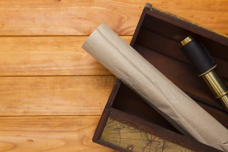 纸卷和望远镜在老箱子 库存照片