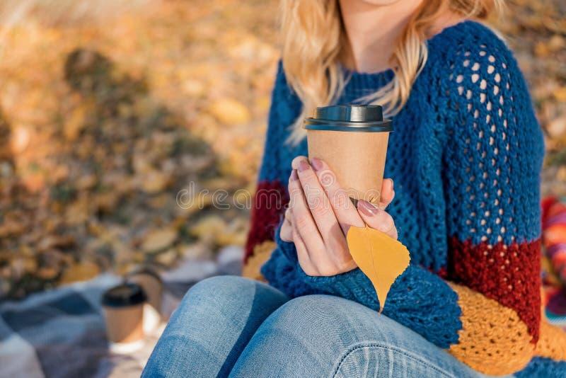 纸咖啡和黄色秋天叶子在可爱的妇女的手上 免版税库存图片