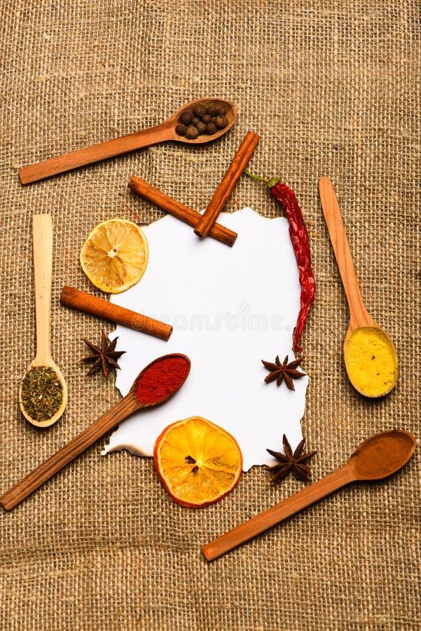 纸在麻袋布背景的 桂香、干桔子和胡椒,在白纸附近的八角食谱的 免版税库存图片
