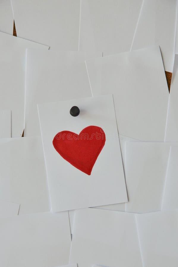 纸在noticeboard的油漆红色心脏 免版税库存图片