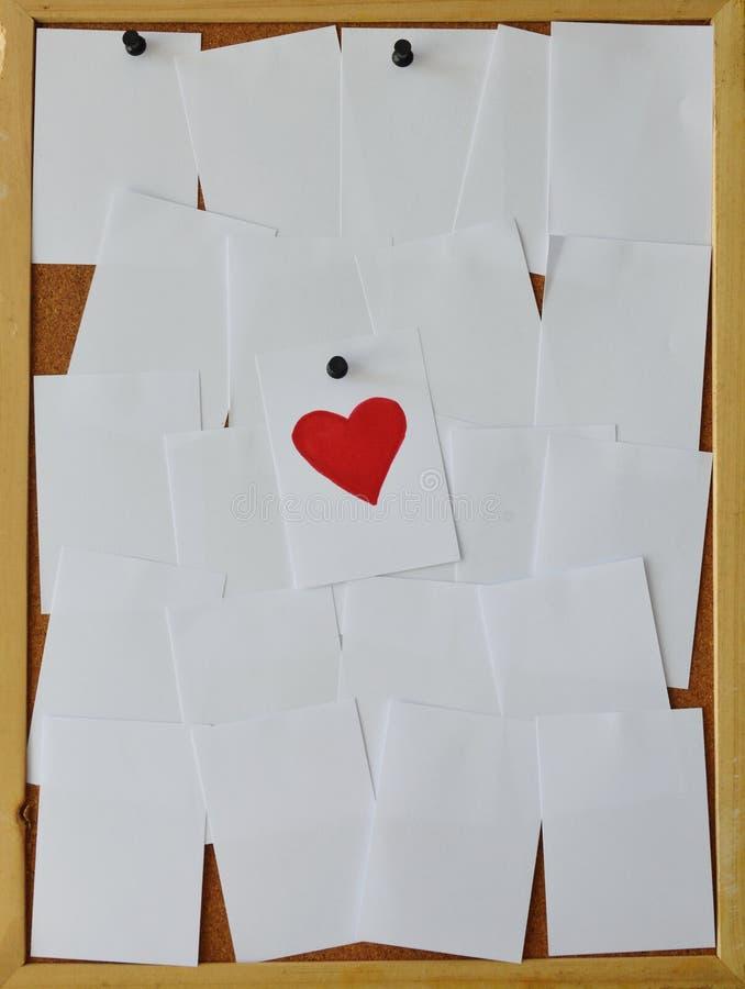 纸在noticeboard的油漆红色心脏 库存图片