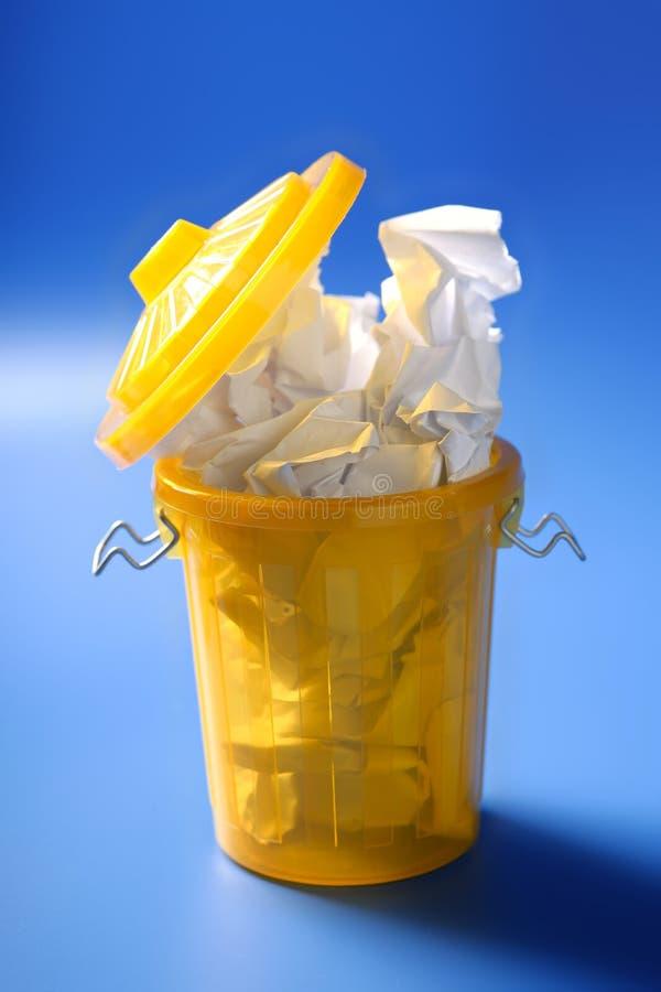 纸垃圾以在蓝色背景的黄色 免版税图库摄影