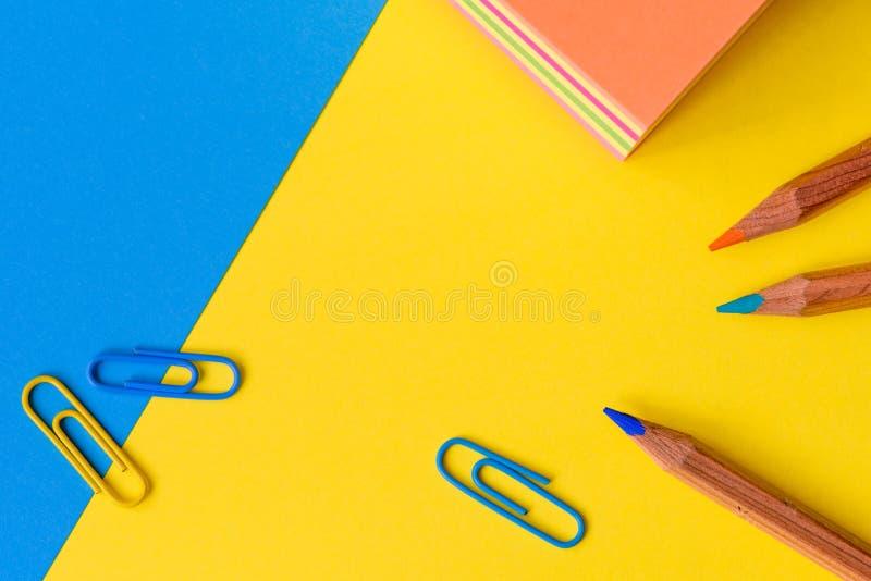 纸夹、铅笔和备忘录块被隔绝反对蓝色和 免版税库存照片