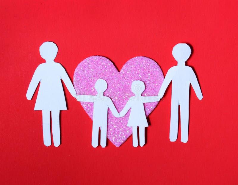 纸家庭在桃红色心脏在红色背景。爱,孩子 免版税库存照片