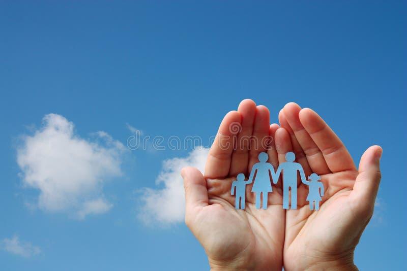 纸家庭在蓝天背景福利救济概念的手上 免版税库存图片